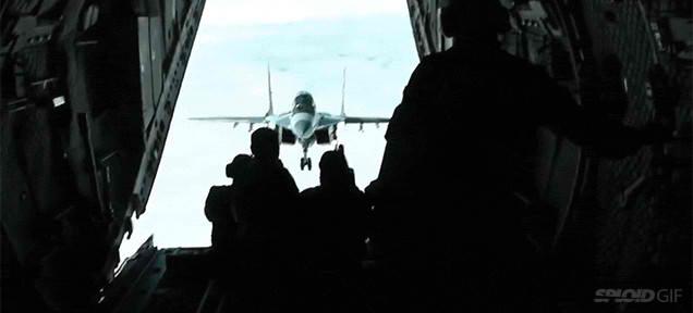 Acest avion cu reactie MiG-29 se aliniaza in fata usii deschise a unui avion de parasutisti